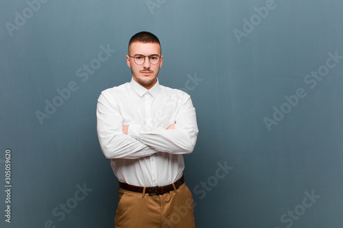 Fototapety, obrazy: young handsome businessman feeling displeased and disappointed, looking serious, annoyed and angry with crossed arms against flat background