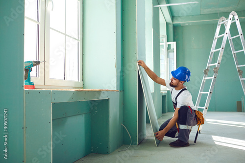 Worker builder installs plasterboard drywall at a construction