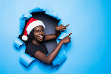 Young African Woman Wear In Santa Hat Pointed With Hand On Copy Space Standing In Blue Torn Paper Hole Background
