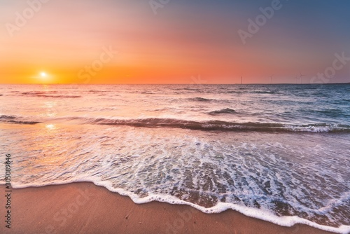 Beautiful view of the ocean waves coming to the shore under the sunset in Zeeland, Netherlands - 305089646