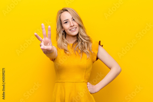 Fotomural young pretty blonde woman smiling and looking friendly, showing number three or