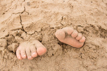 Feet Buried In Sand On The Coast Of Scotland On A Sunny Day.