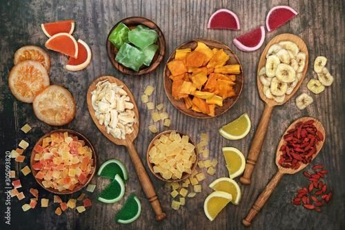 Dried fruit selection in wooden spoons & bowls on rustic wood background. Health food high in antioxidants, minerals, vitamins and anthocyanins. Flat lay., top view.