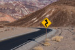 canvas print picture - A crooked road sign along a highway curving through a barren and rugged desert landscape