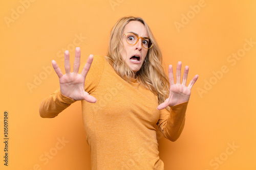 Fotografia young pretty blonde woman feeling terrified, backing off and screaming in horror