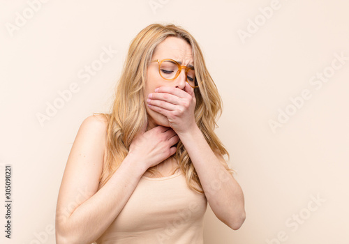 young pretty blonde woman feeling ill with a sore throat and flu symptoms, cough Wallpaper Mural