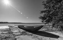 Small Boat On Pond Shore. Artistic Black And White Scene. Natural Still Life. Fishing Vessel On Concrete Pier, Tree, Rippled Water Surface And Sunbeams On Sky Above Horizon. Czech Horusicky Fishpond.