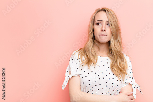 young pretty blonde woman doubting or thinking, biting lip and feeling insecure Wallpaper Mural