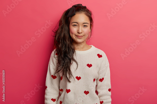 Valokuva Beautiful tender Asian girl with long pony tail, rouge cheeks, wears comfortable jumper with hearts, stands against pink background, looks directly at camera, has dimples on cheeks