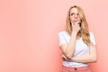 Young Pretty Blonde Woman Thinking, Feeling Doubtful And Confused, With Different Options, Wondering Which Decision To Make Against Flat Color Wall