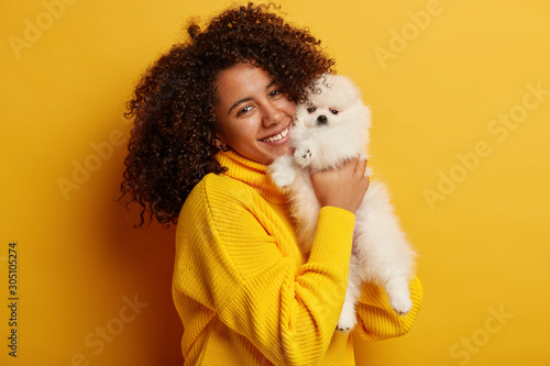 Isolated shot of beautiful lady with Afro hairstyle, embraces tightly and holds spitz dog near face, poses with small beloved white puppy isolated over yellow wall Fototapete