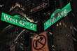 Intersection of 42nd street and 5th avenue with 42nd street and 5th avenue street signs in New York during the night