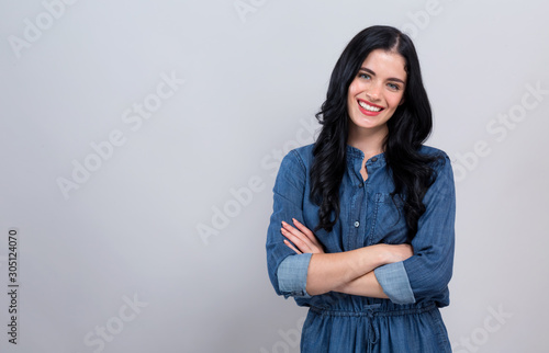 Young woman with crossed arms on a gray background Canvas Print