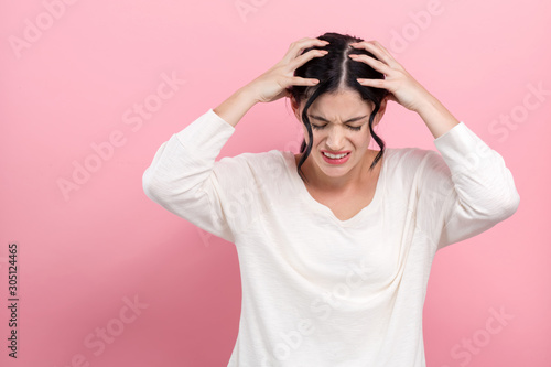 Young woman suffering from headache on a pink background Canvas-taulu