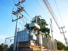 Large Transformers Installed On The Side Of The Road With A High Voltage Cable On The Pole And Surrounded By A Metal Fence On The Background Of Green Trees And Blue Skies