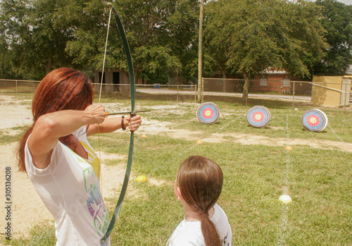 Mother and daughter doing archery Canvas Print