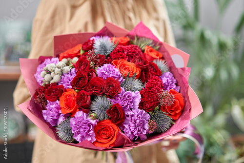 Modern floral shop. Finished work of the florist. Cute bouquet of mixed flowers in womans hands. Delivery fresh cut flower. © malkovkosta