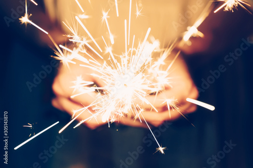 Fotografie, Tablou  Close up hand woman holding sparklers in night party and christmas celebration