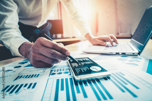 Fotografie, Obraz Businessman accountant or financial expert analyze business report graph and finance chart at corporate office