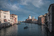 Venice Grand canal on sunset time. View of Basilica di Santa Maria della Salute, gondolas, water buses and typical Venetian houses and architecture. Beautiful and romantic Italian city.