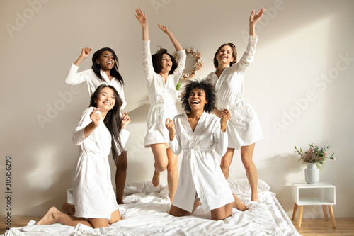 Foto Excited multiracial girls friends having fun dancing on bed