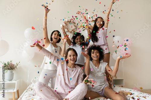 Obraz Smiling women group wear sleepwear celebrate party throw confetti up - fototapety do salonu