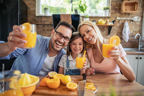 Cheerful young family drinking orange juice - 305170666