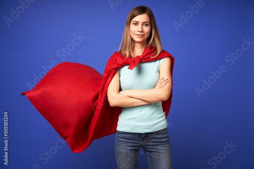 Fotografía Woman in red superhero cloak standing on empty blue background