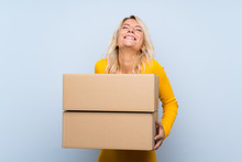 Young Blonde Woman Over Isolated Background Holding A Box To Move It To Another Site