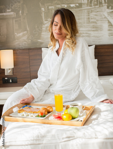 Fototapeta Attractive woman having breakfast in hotel bed obraz