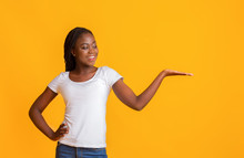 Smiling Woman With Her Palm Up Over Yellow Background