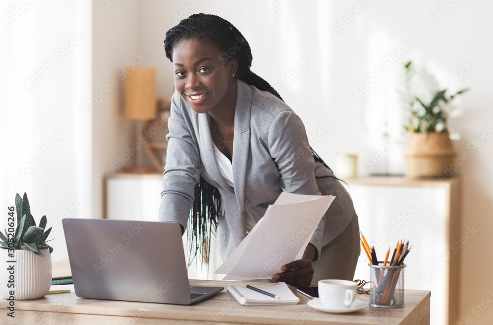 Fototapeta Afro Businesswoman Working With Documentation And Laptop In Modern Office