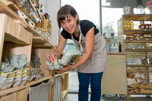 Young Shopkeeper Filling Shelves Of Zero Waste Store With Domestic Products.