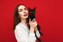 Portrait Of Happy Girl With Black Cat In Hands On Red Background, Smiling And Posing At Camera. Cute Positive Lady In White Shirt With Pet In Hands Isolated On Red Background.