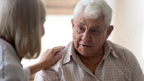Papel de parede Pleasant older man thanking middle aged nurse for psychological help