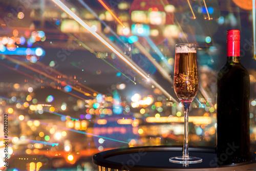 Obraz na plátně  A glass of rose wine over light city blurred background and fireworks, Christmas festive celebration