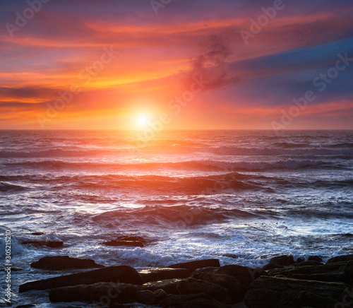 Foto auf Leinwand Hochrote Amazing romantic seascape of ocean coastline at sunset. Landscape of colorful cloudy sky and foamy waves. Concept of harmony with wildlife. Portugal.
