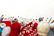 A Beautiful Composition With Knitting Accessories, Balls Of Woolen Yarn, Knitting Needles, Crochets And Handmade Knitted Scarves. Needlework Concept, Place For Text, White Background, Flat Lay