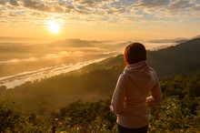 Asian Woman Standing, Watching The Sunrise And The Sea Of Mist At The Mekong River, Thailand