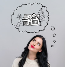 Dreaming Of New Home With Happy Young Woman On A Gray Background