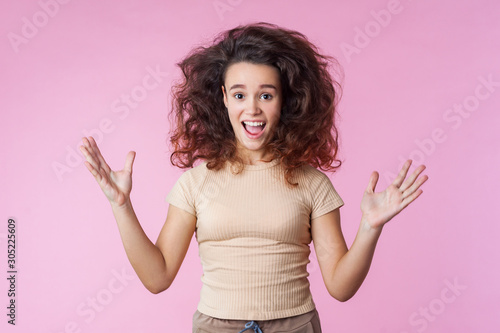 Fototapeta  Portrait of crazy enthusiastic teenage girl with disheveled curly brunette hair flying up and in casual clothes raising hands, shouting in delight, overwhelmed with excitement