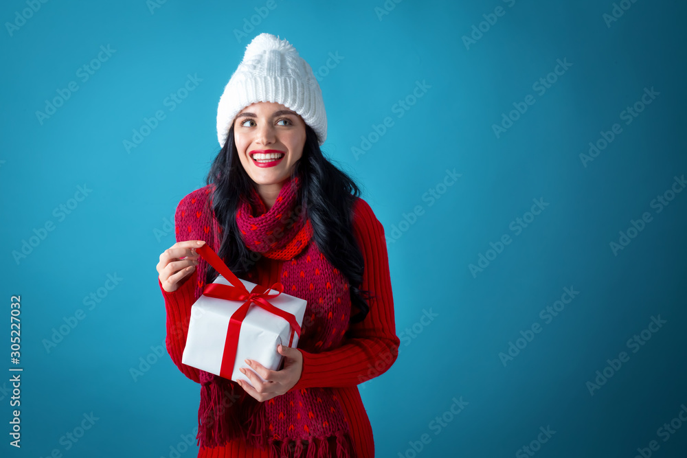 Fotografie, Tablou  Young woman holding a gift box on a dark blue background