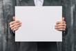 Leinwanddruck Bild - business man holding a blank poster