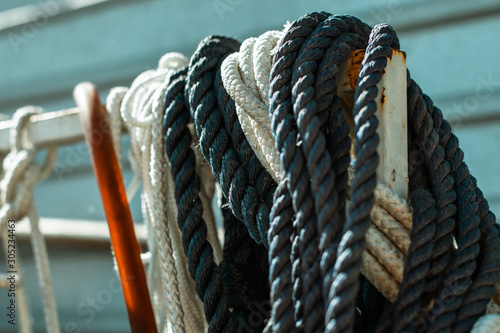 Foto auf AluDibond Schiff Ropes hang on a metal bar. Anchor rope hanging on the iron rod