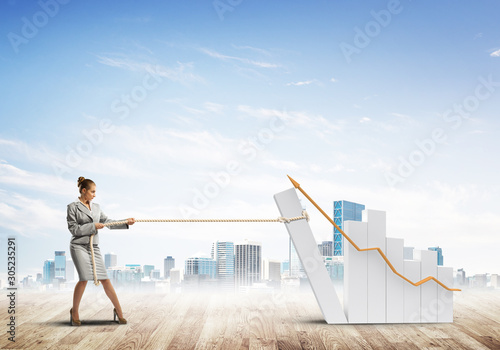 Businesswoman pulling graph with rope as concept of power and control Wallpaper Mural