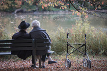 Senior Couple Man And Woman Are Resting On A Bench In The Autumn Park. Effect Neutral And Pastel Color Images.