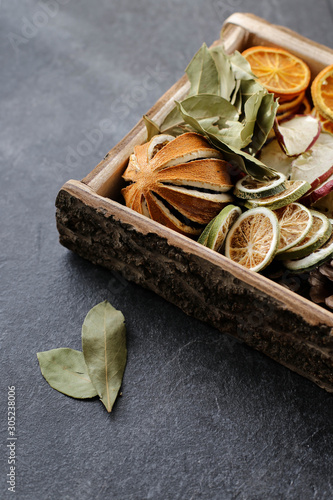 Tablou Canvas A set of dried spices and fruits for a Christmas decoration or for a Christmas drink in a wooden stand, on a dark relief background