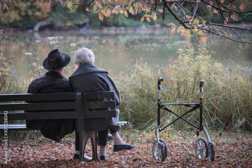 Senior couple man and woman are resting on a bench in the autumn park. Effect neutral and pastel color images. #305238042