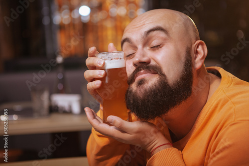 Photo Close up of a happy bearded man cuddling with a glass of beer