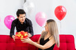 Attractive young couple celebrate anniversary, together. Man giving present gift box to woman.